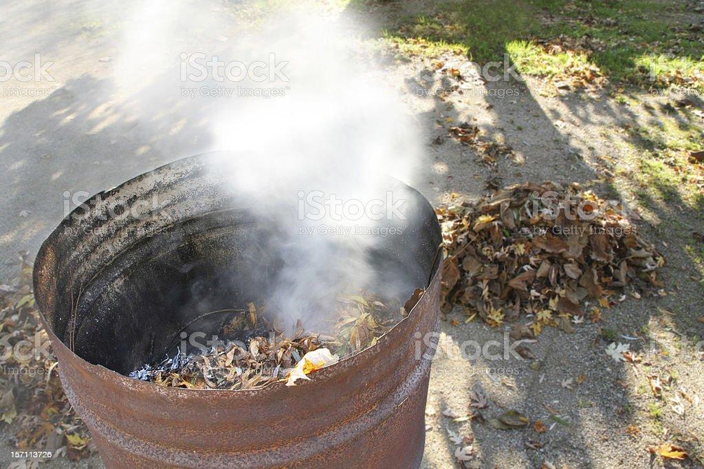 Burning autumn leaves gardening in rusty barrel stock photo