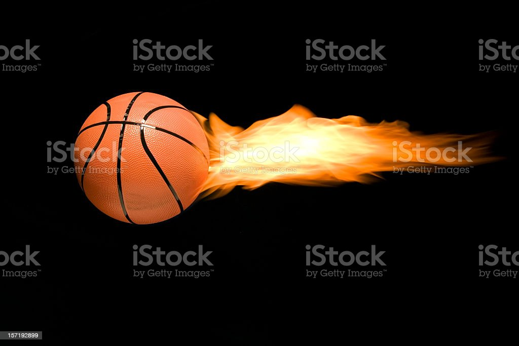 A burning basketball flying through the air stock photo