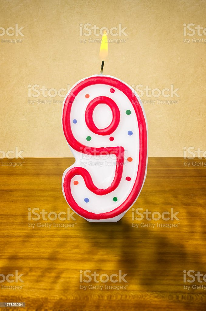 Burning birthday candle number 9 stock photo