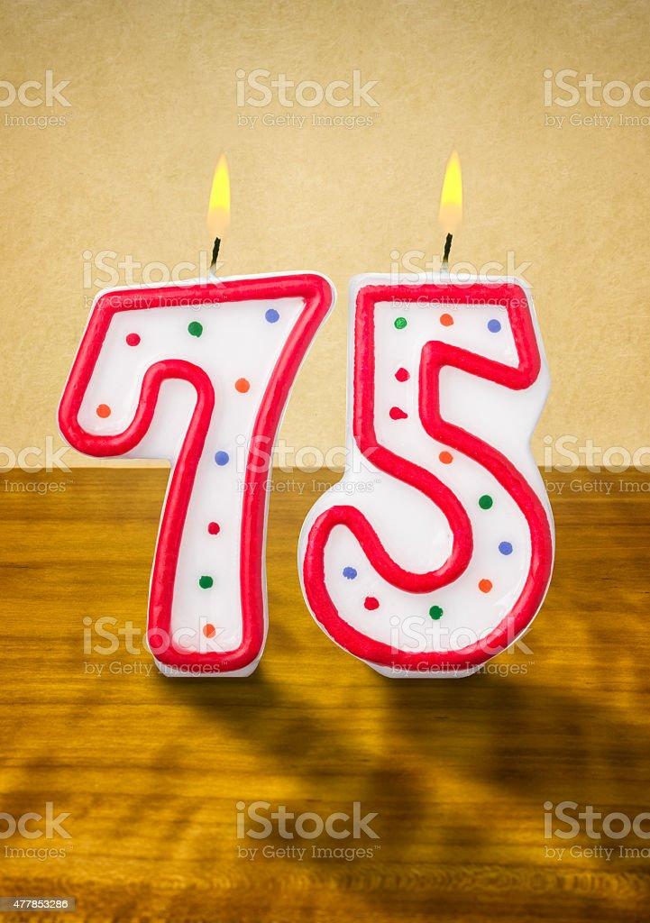 Burning birthday candles number 75 stock photo