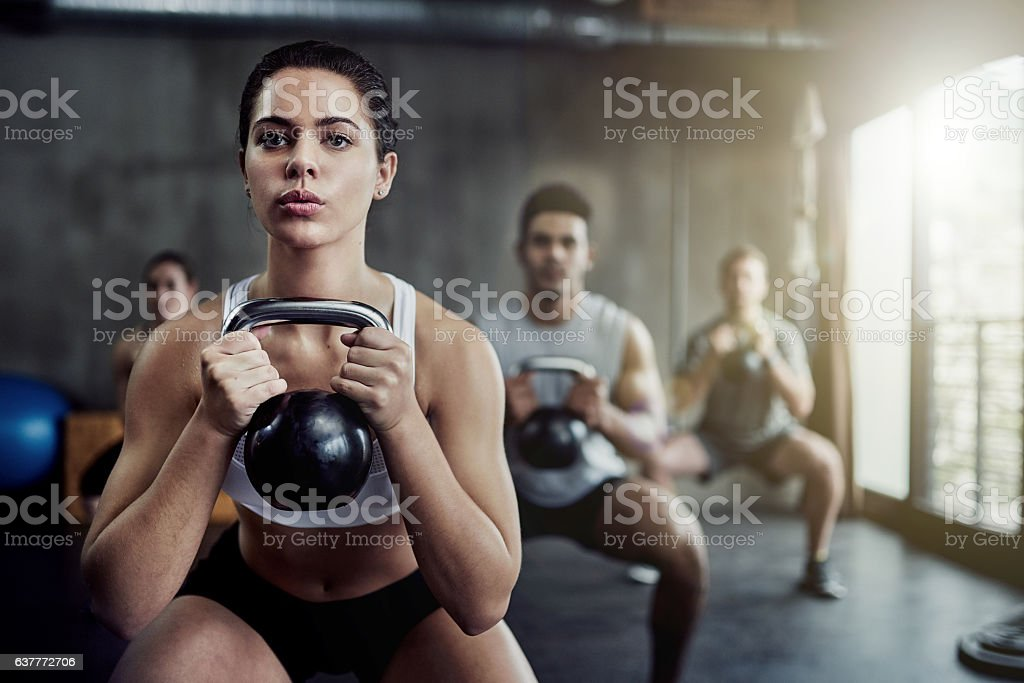 Burning calories and strengthening her core with a kettlebell stock photo