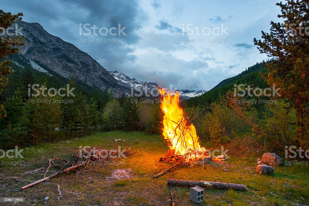 Burning camp fire in alpine woodland with dramatic sky stock photo