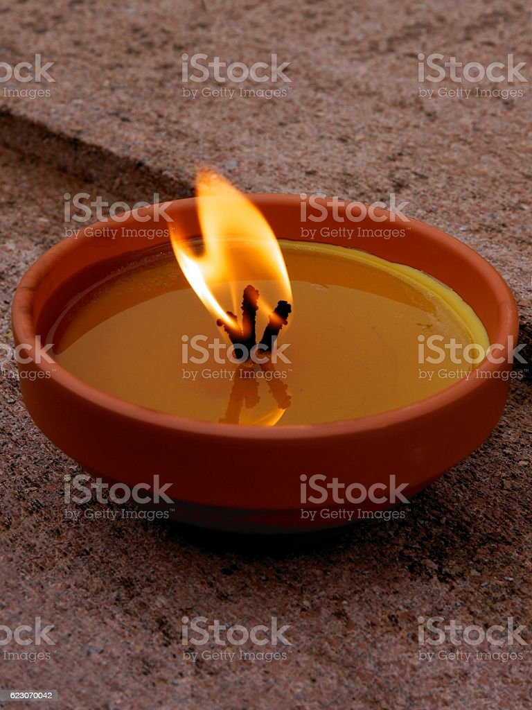 burning candel on tomb in cemetery stock photo