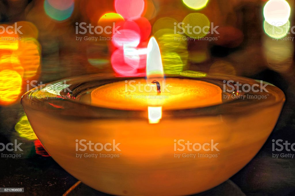 burning candle and colorful lights stock photo