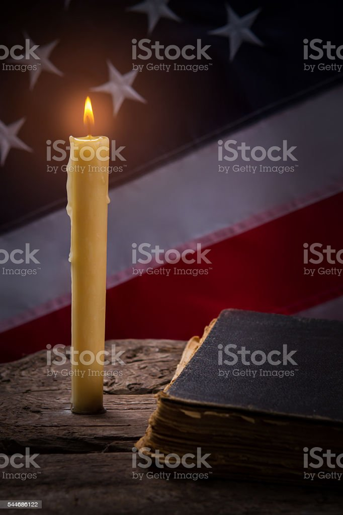 Burning candle and old book. stock photo