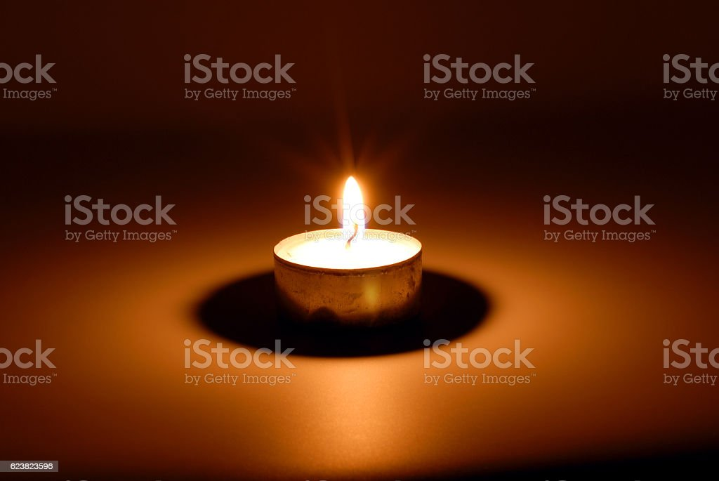 Burning candle in darkness stock photo