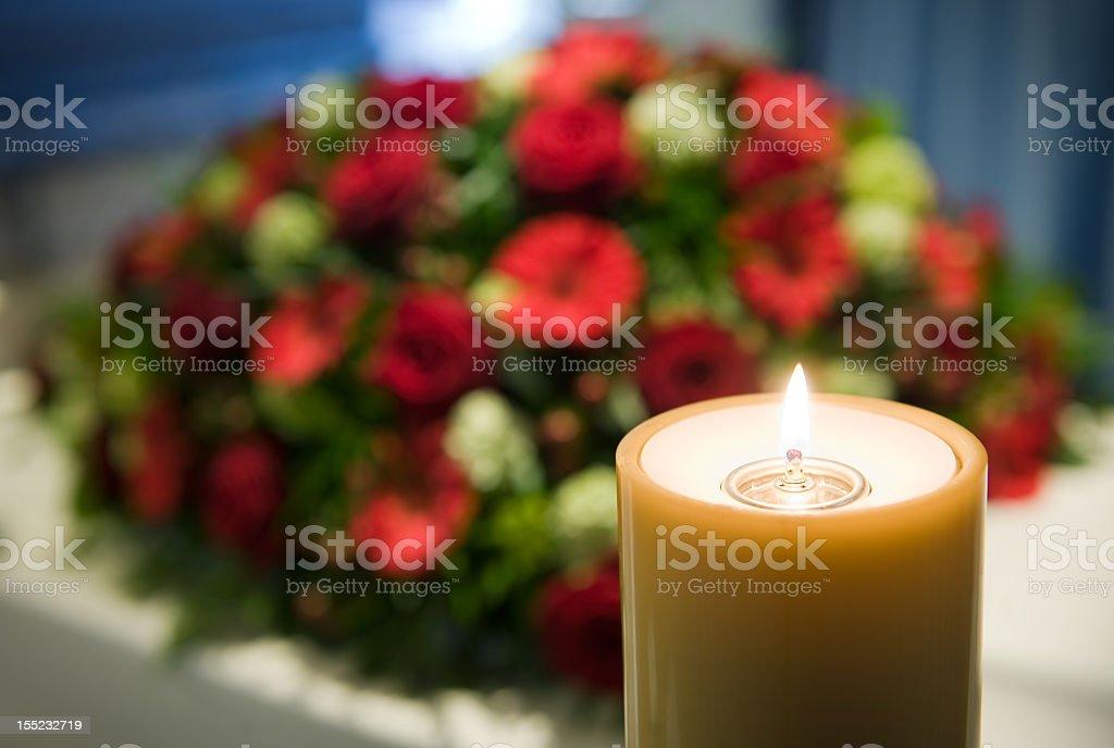 Burning candle next to bundle of flowers stock photo