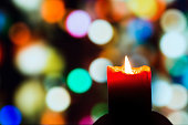 Burning candle on a background of colorful circles.