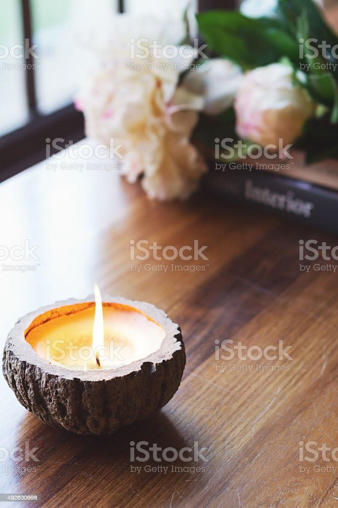 Burning candle on buffet home interior stock photo