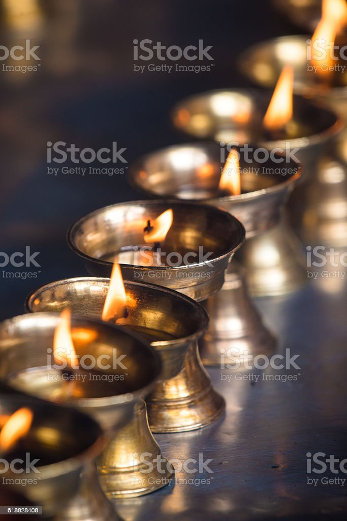 Burning candles lighting up at Buddhist temple stock photo