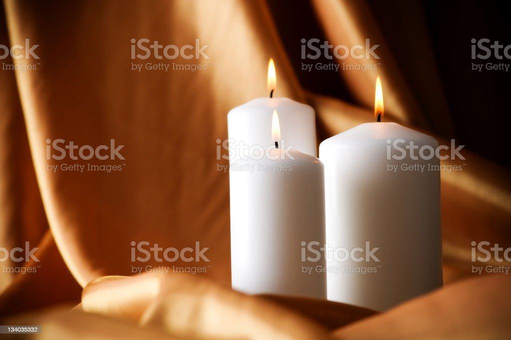 Burning candles on satin background royalty-free stock photo