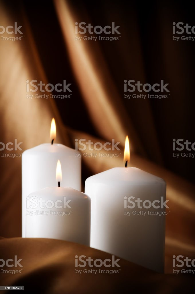 Burning candles on satin background royalty-free stock photo