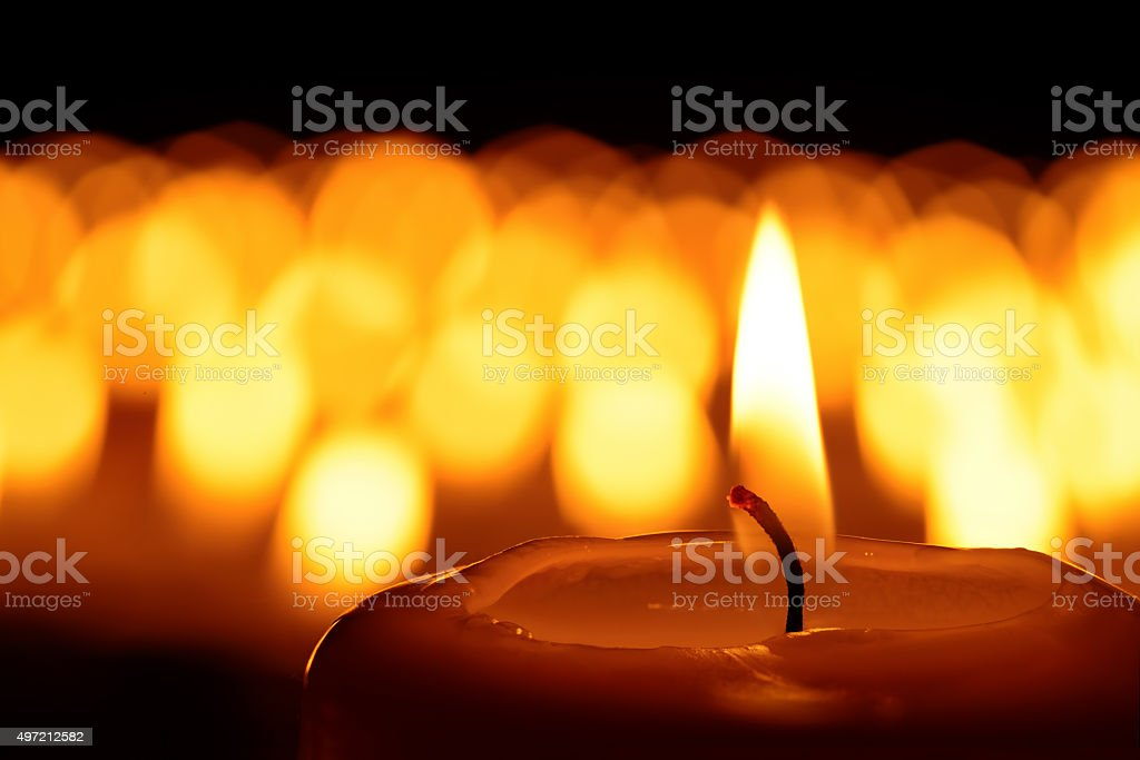 Candle in front of many defocused candleflames creating a spiritual...