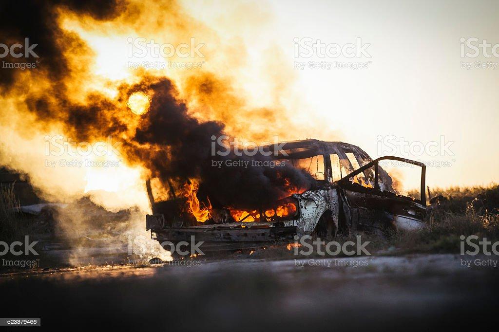 Burning car covered in black smoke stock photo