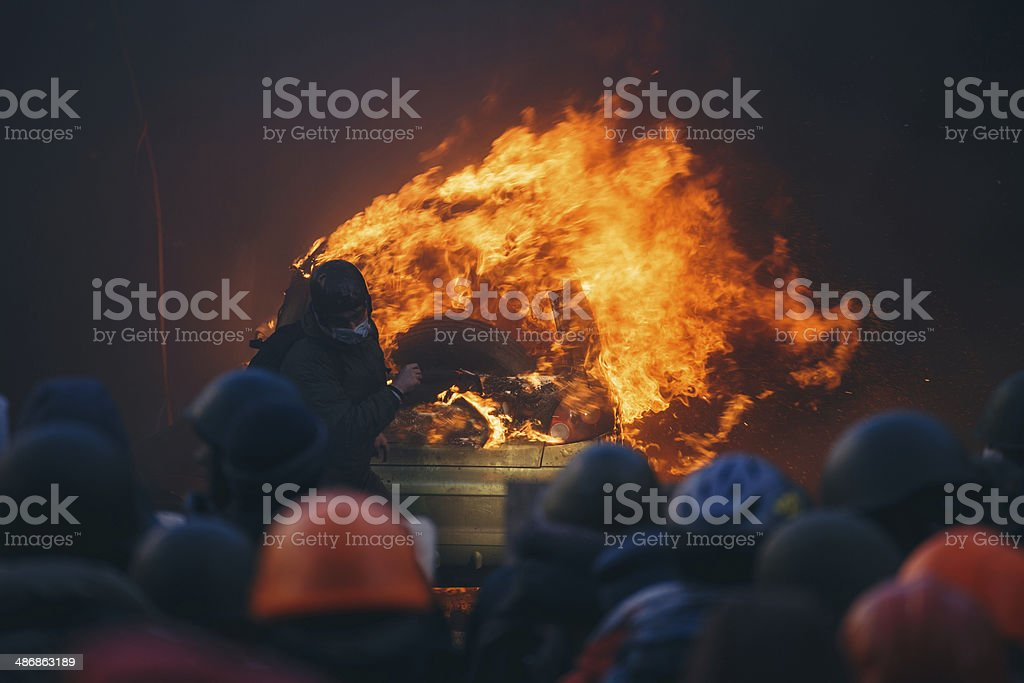 Burning car during anti-government riot stock photo
