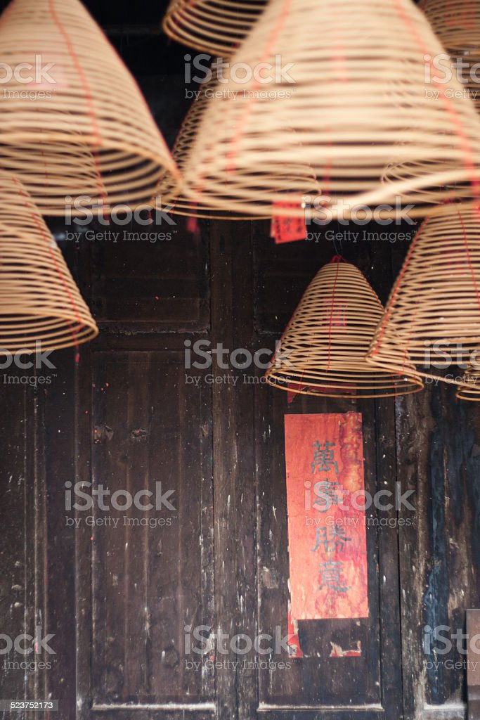 burning chinese circular joss sticks and couplet stock photo