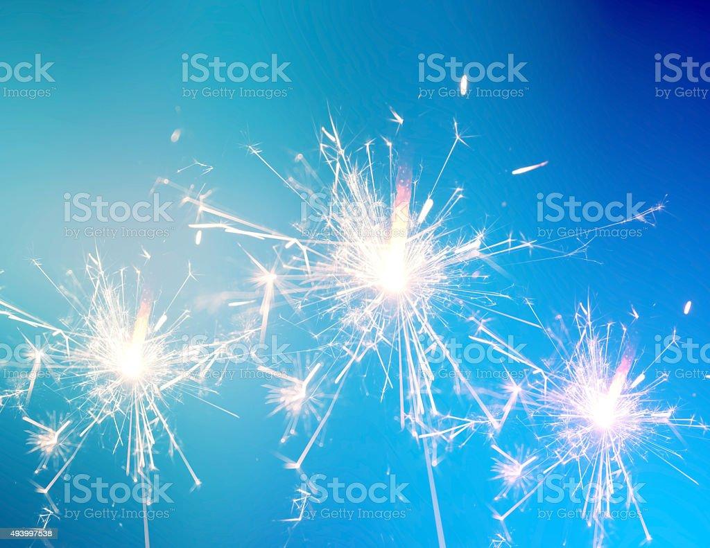 Burning christmas sparkler on blue background stock photo