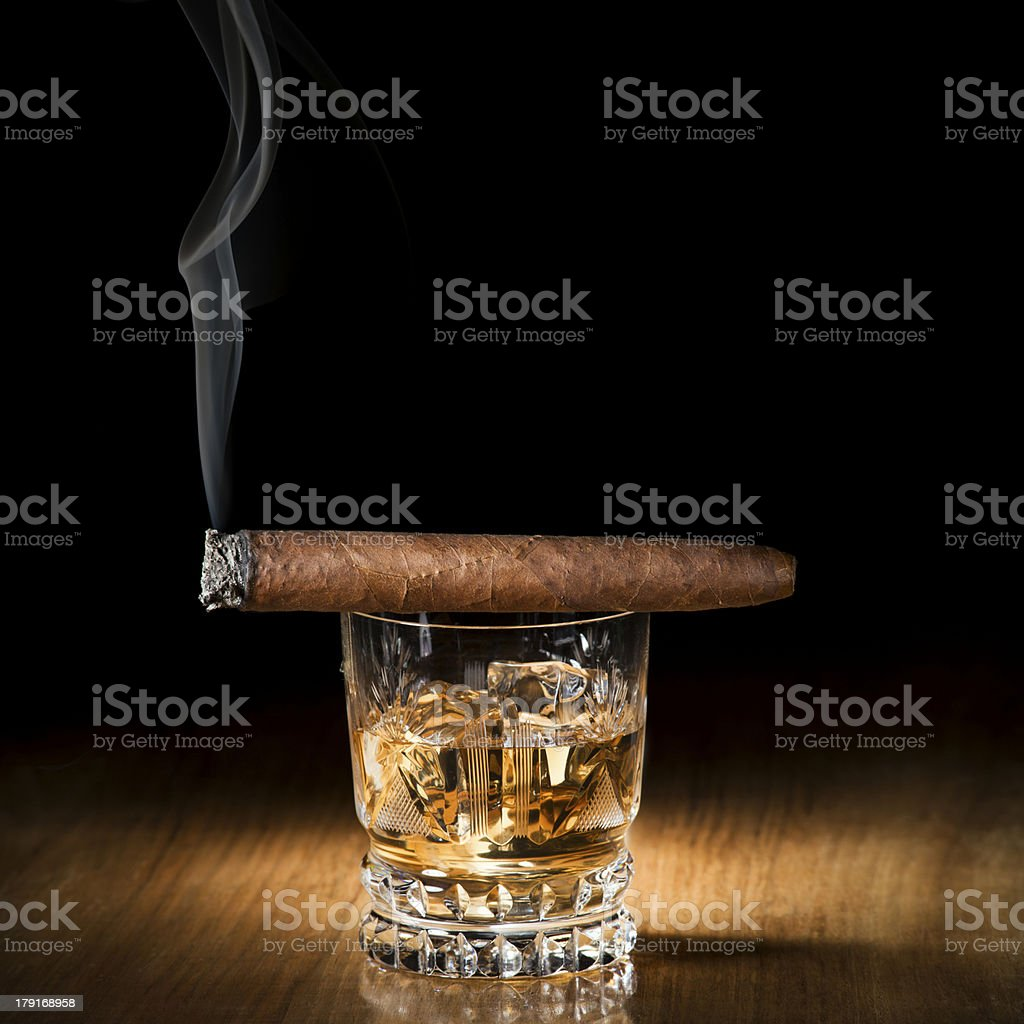 A burning cigar on top of a glass of alcoholic drink stock photo