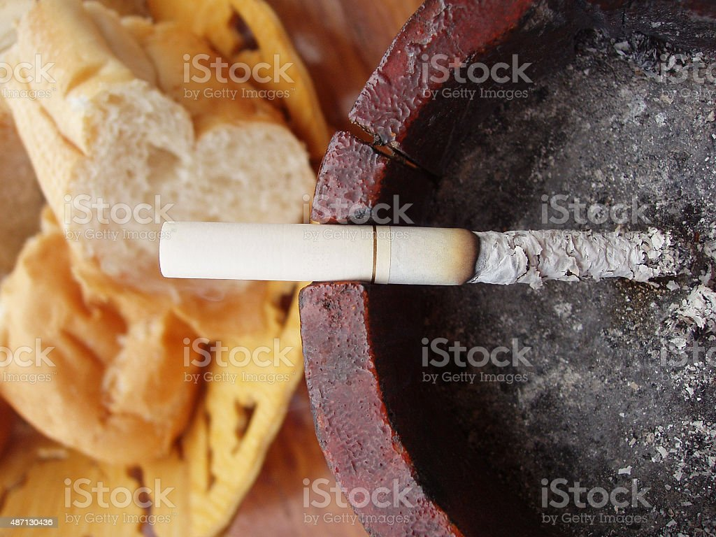Burning Cigarette in an Ashtray Next to Breakfast Bread Basket royalty-free stock photo
