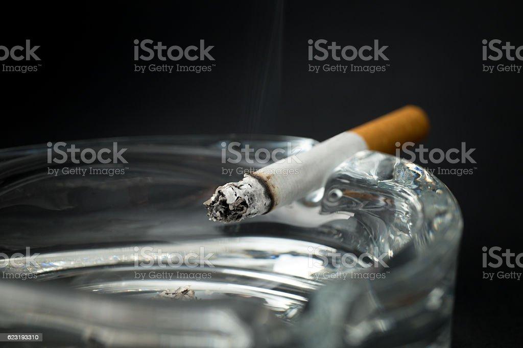Burning cigarette with ashtray stock photo
