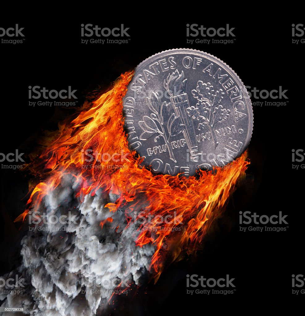 Burning coin with a trail of fire and smoke stock photo