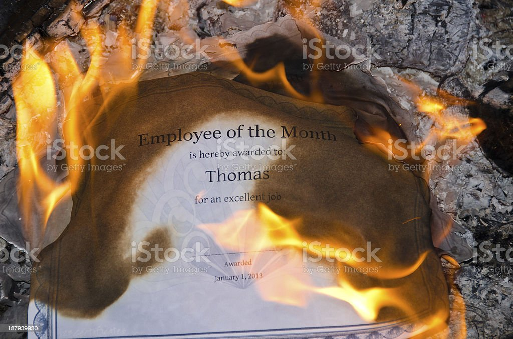 Burning employee of the month certificate against rocks stock photo