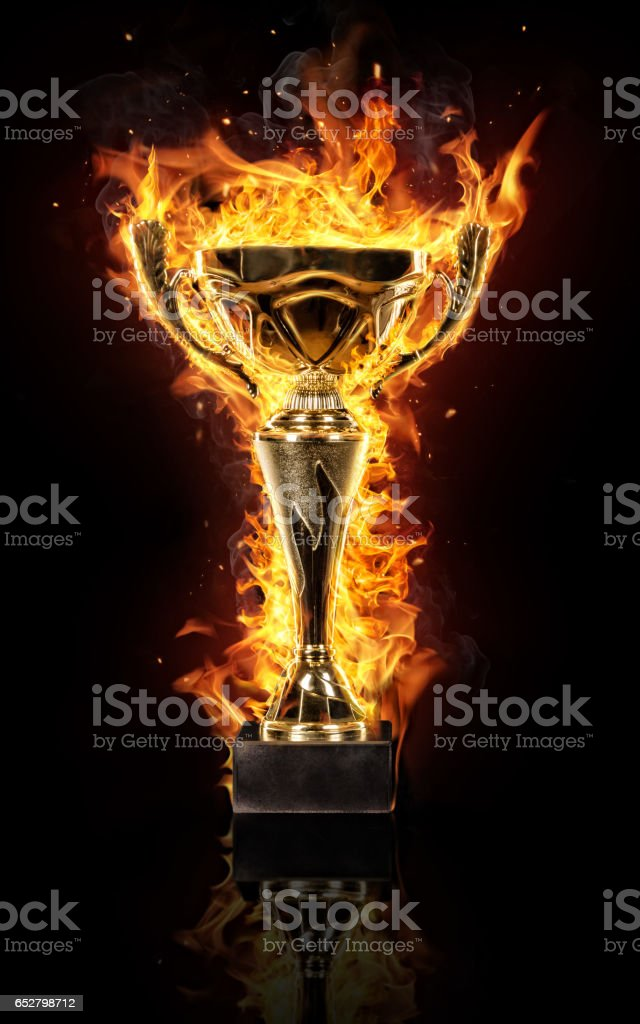 Burning gold trophy cup on black background stock photo