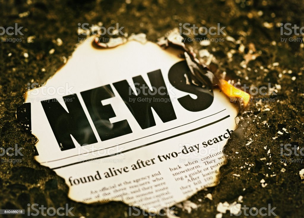 Burning headlines as newspaper catches fire stock photo