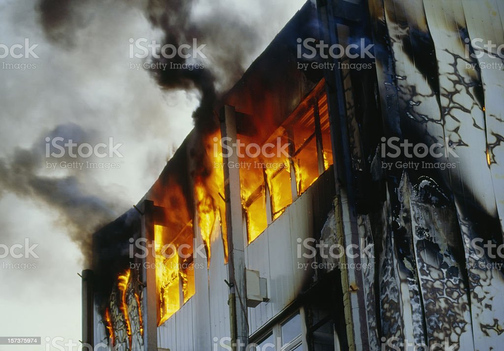 Burning house upper floor and and ascending black smoke royalty-free stock photo