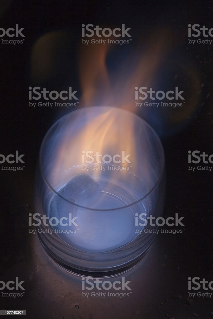 Burning ice cube in a whiskey glass stock photo