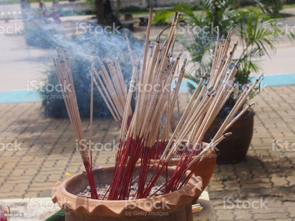 burning incense sticks in ashes earthenware pot with waving smoking stock photo