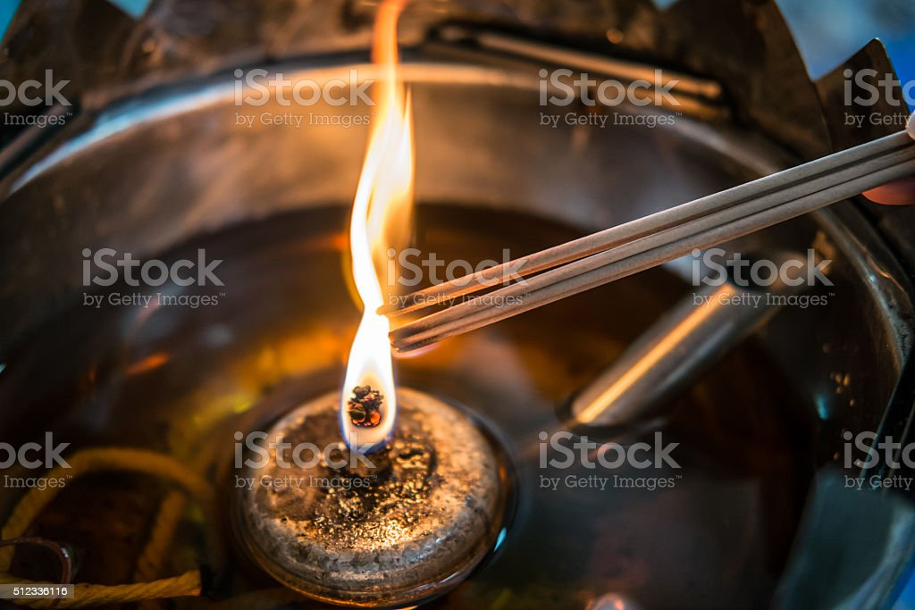 Burning incense sticks on a yellow candle flame, selective focus stock photo