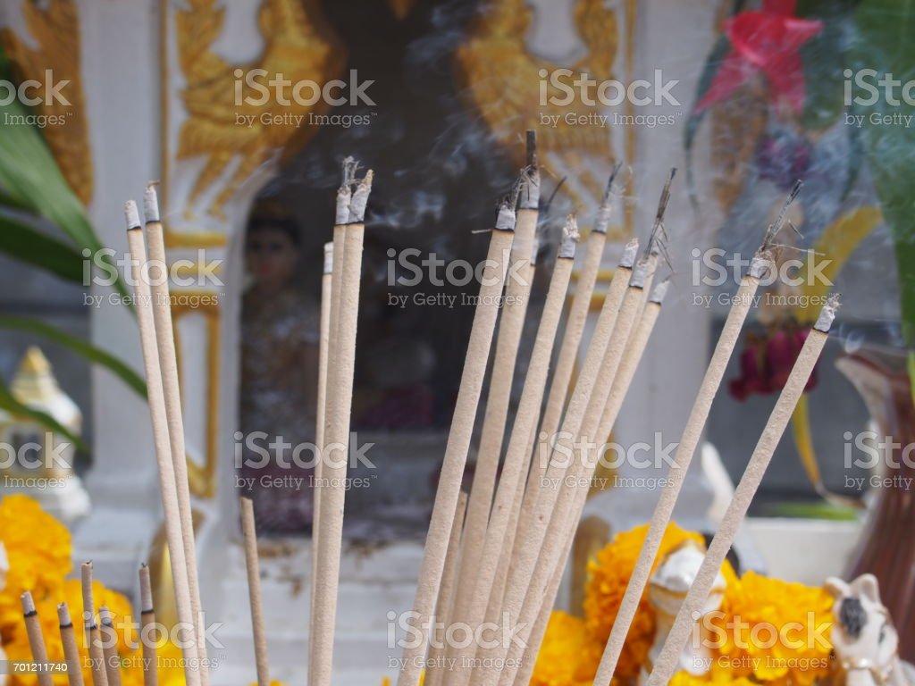 burning incense sticks on blurred background of spirit house with waving smoking stock photo