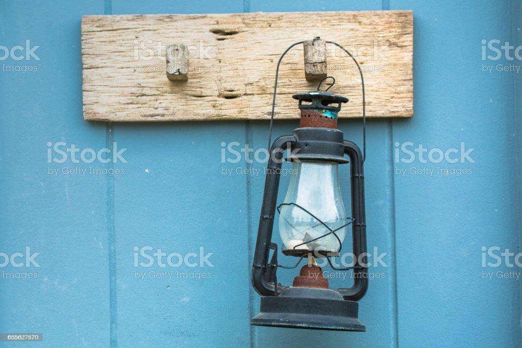 Burning kerosene lamp hang on the wooden wall stock photo