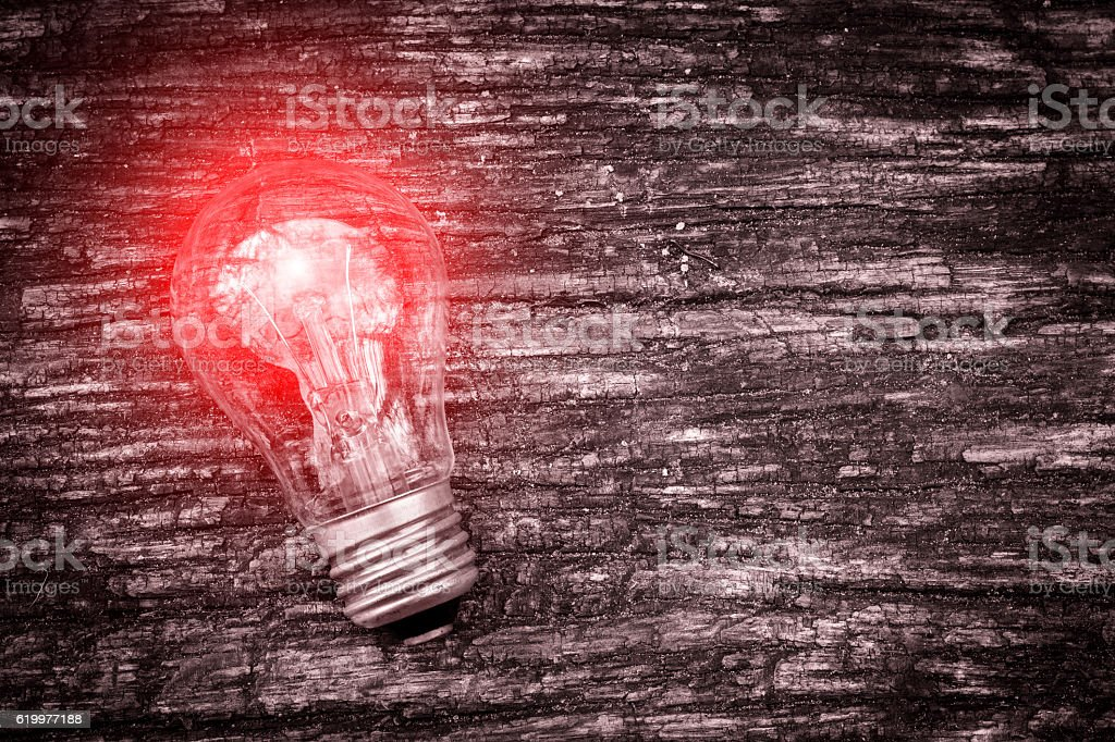 Burning light bulb on dark old wooden background. Business idea. stock photo