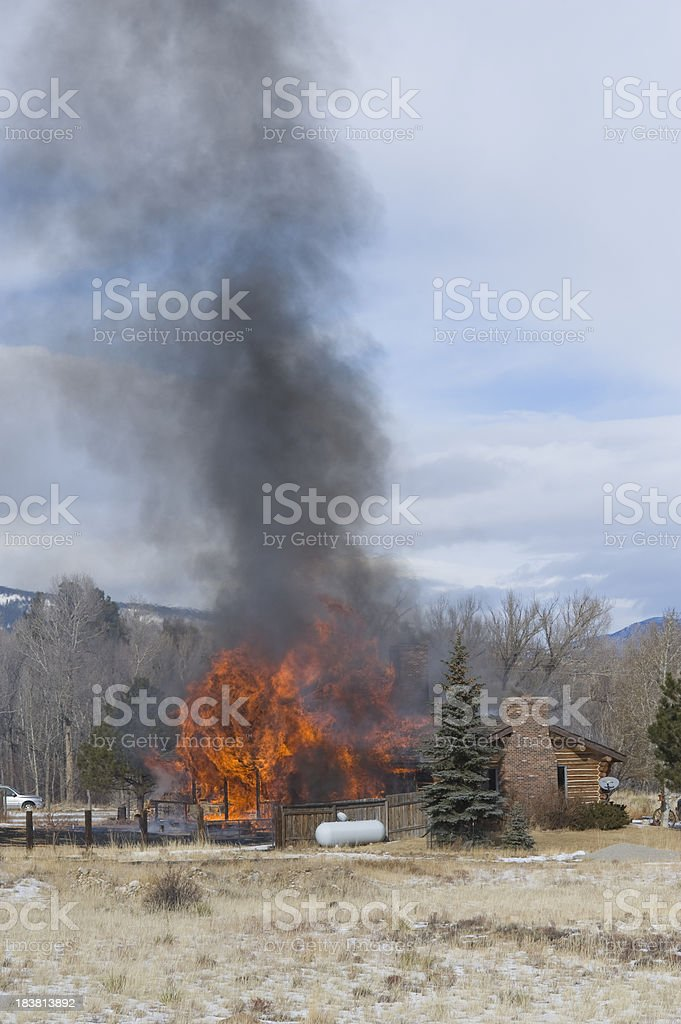 Burning Log Cabin in the Mountains stock photo