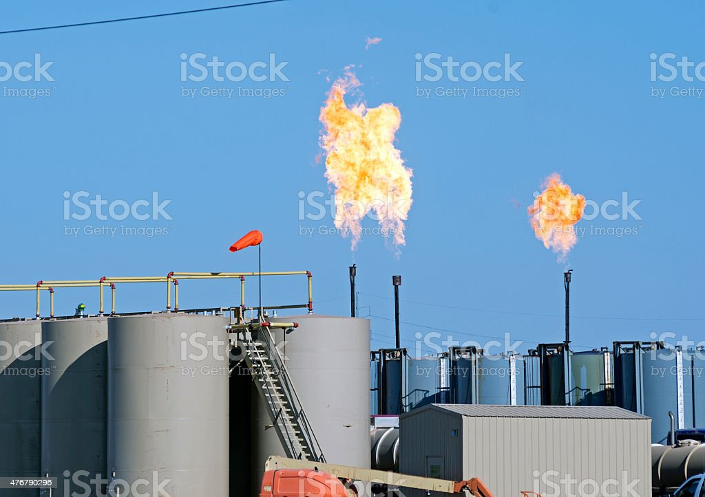 Burning off gas from oil storage tanks in North Dakota stock photo