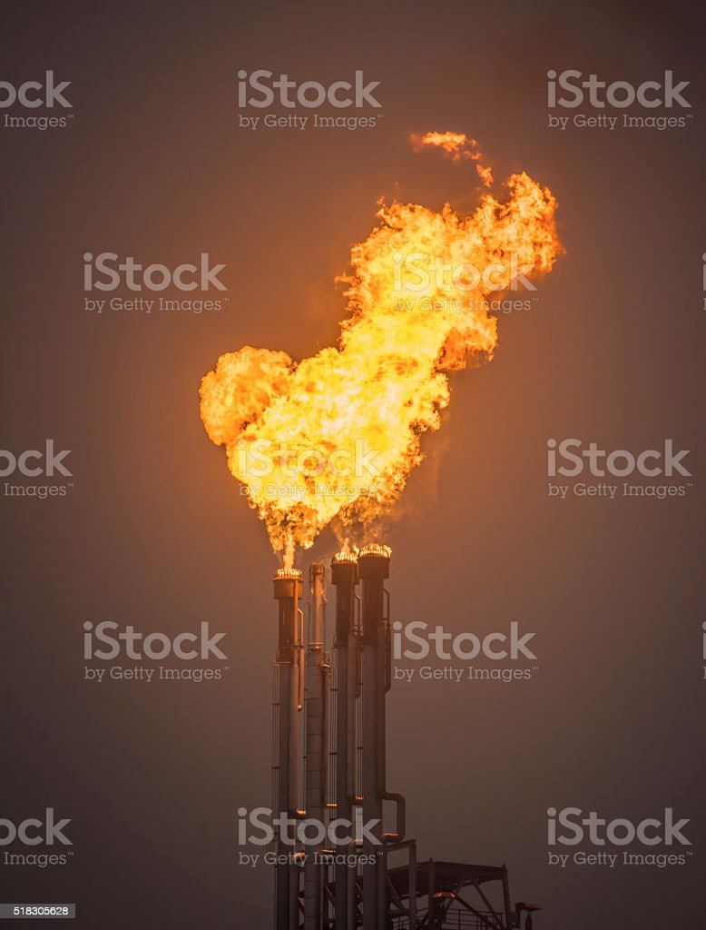 Burning oil gas flare in a large oil refinery stock photo