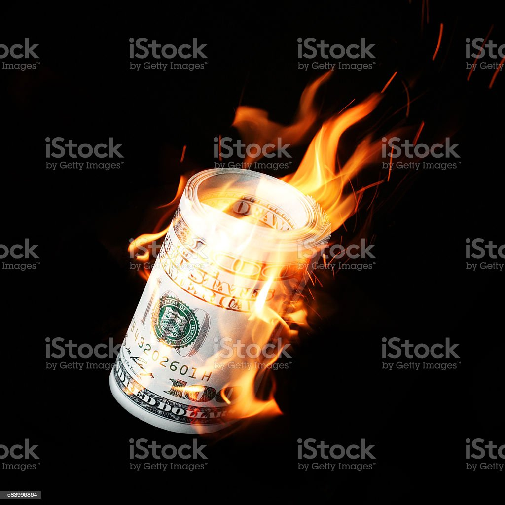Burning one hundred dollar bills rolled stock photo