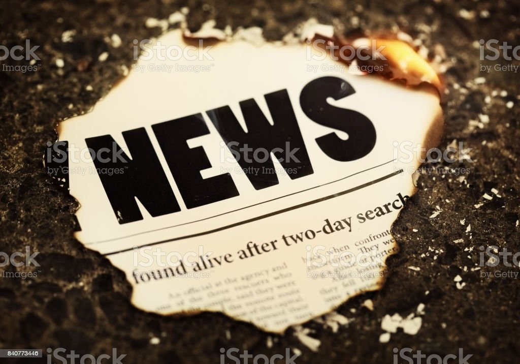 Burning scrap of news headlines with dramatic rescue story stock photo