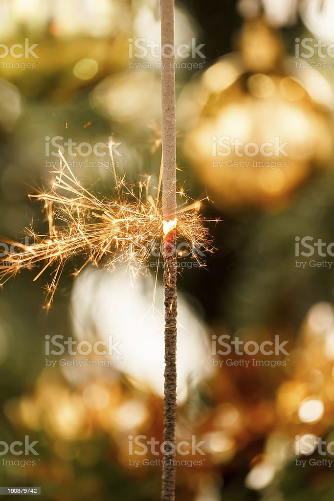 burning sparkler and out of focus christmas tree royalty-free stock photo