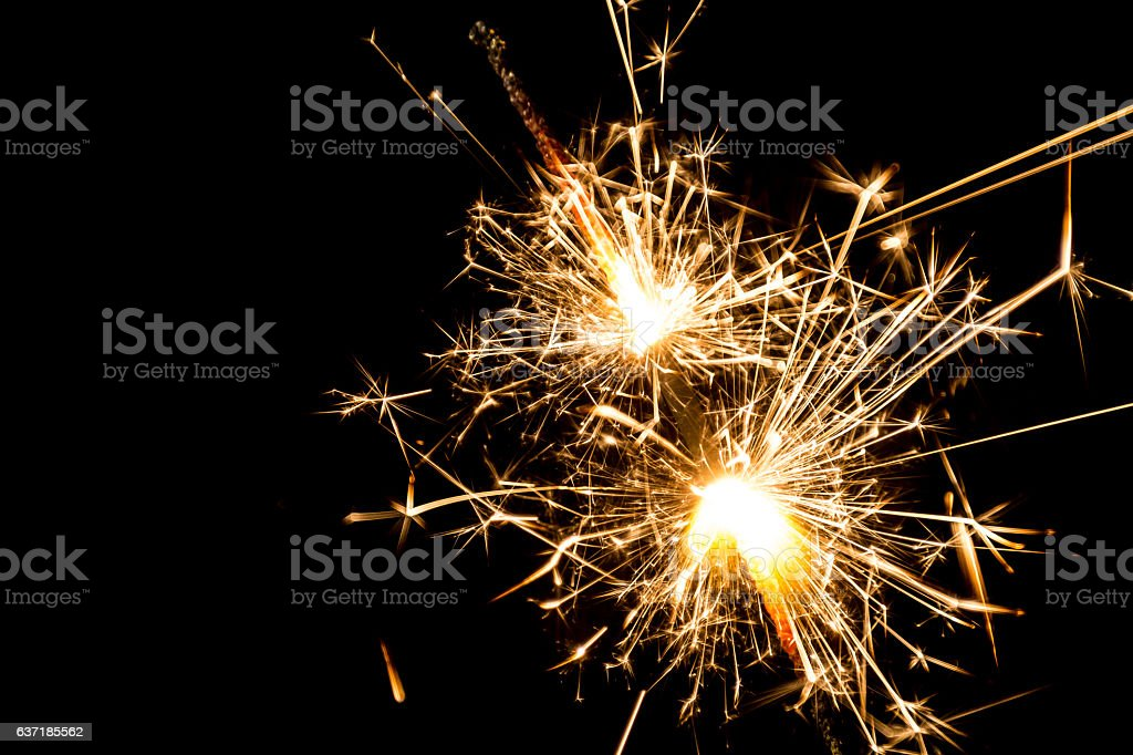 Burning sparkler from both ends at black background stock photo
