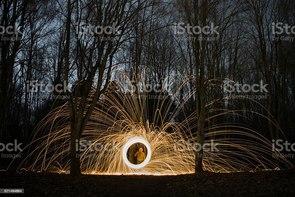 Burning steel wool spinned near the sea stock photo