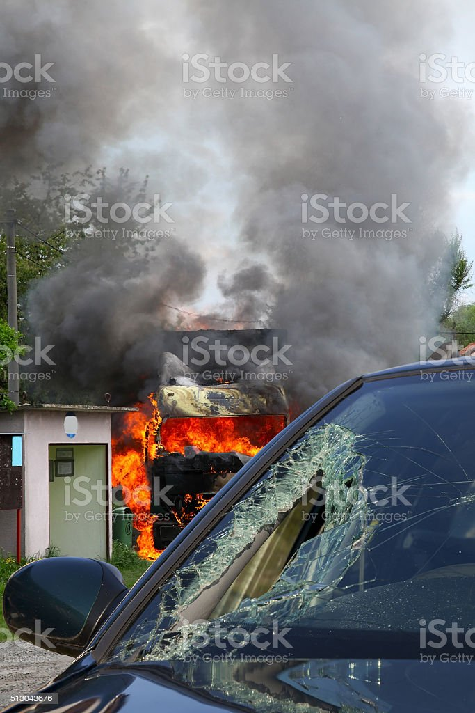 Burning truck in an accident with car, broken glass stock photo