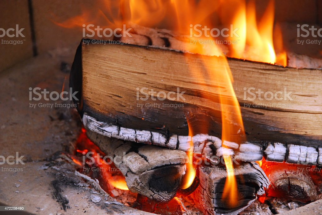 Burning wood with flame inside of a hearth stock photo