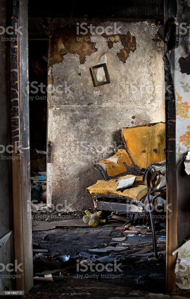 Burnt, Damaged Interior of Home with Destroyed Chair and Books stock photo