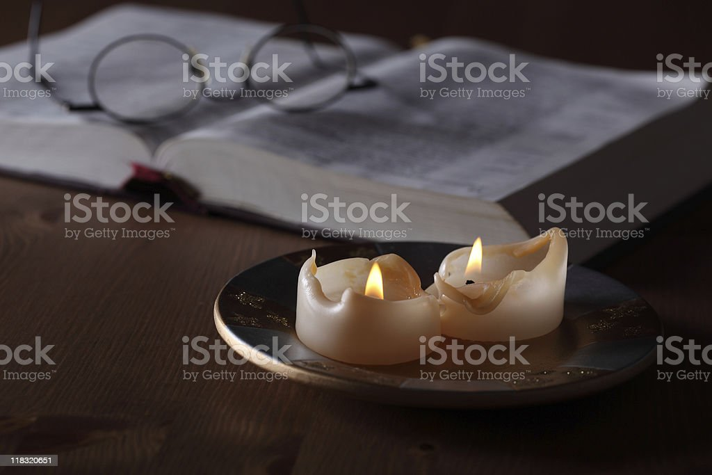 Burnt down Candles and Bible Reading Lowlight royalty-free stock photo