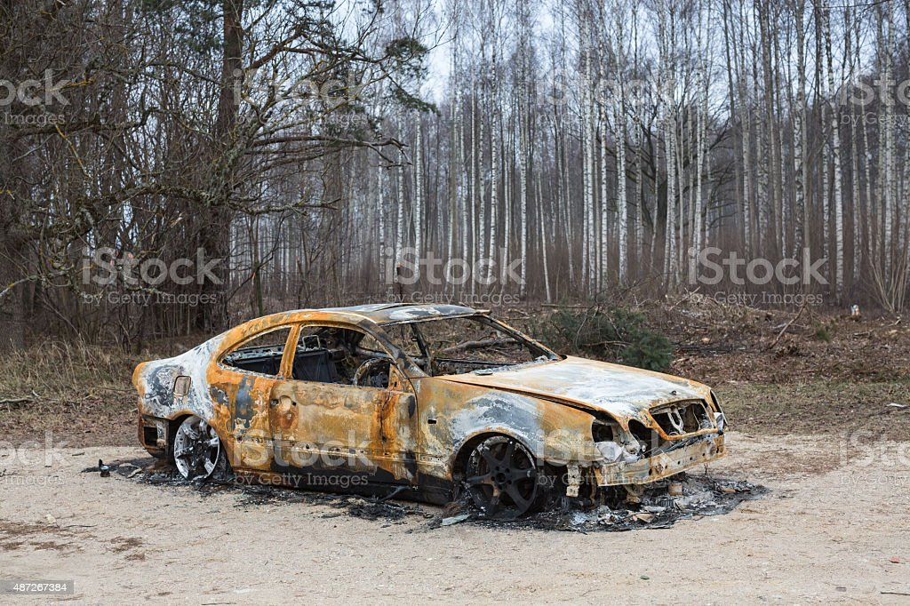Burnt out rusted old car near the road and forest stock photo