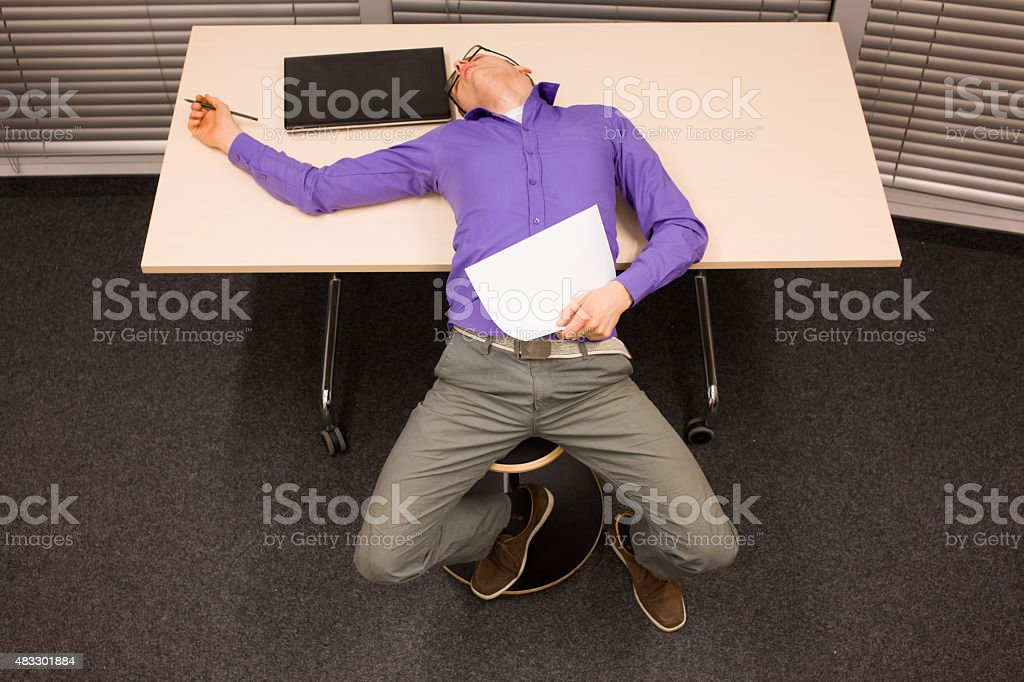 burnt out white collar worker laying on the table stock photo