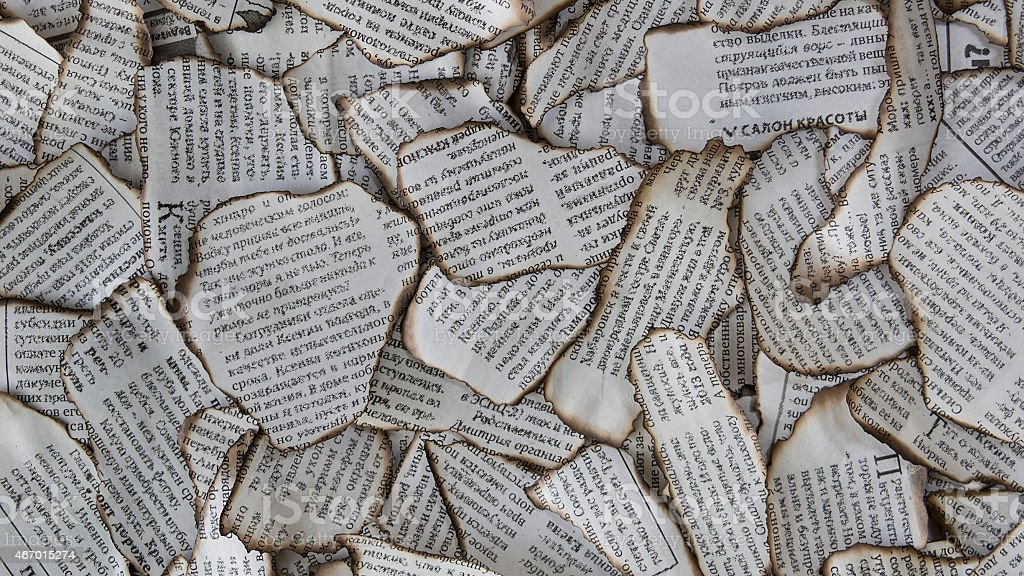 Burnt scraps of newspaper for background stock photo